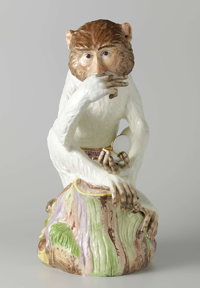this is a porcelain monkey holding a snuff box.