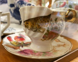 tea cup and saucer with a perch and some parrots